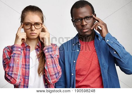 Two People Posing At Studio Wall: Cute European Girl And African American Guy Holding Fingers On Tem
