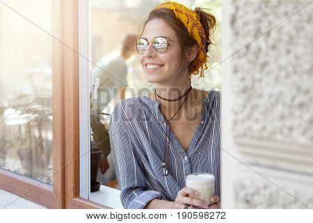 Caucasian Woman Wearing Yellow Scarf On Her Head, Sunglasses And Stripped Shirt Looking Out Of Windo