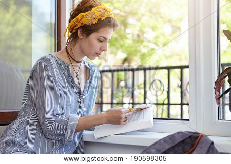 Pleasant-looking Woman Wearing Loose Shirt And Yellow Headband Sitting Near Opened Window Reading Bo