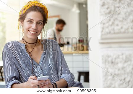 Woman With Beautiful Appearance Wearing Yellow Headband And Stripped Shirt Leaning On Table While Ho