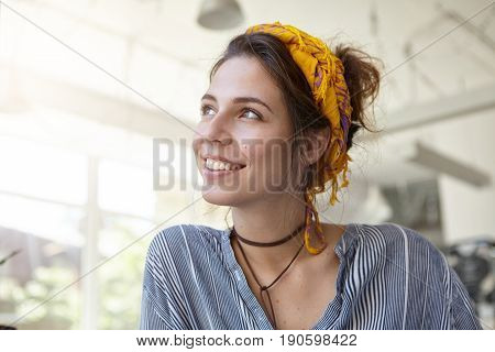 Sideways Portrait Of Beautiful Caucasian Woman With Headband On Head And Casual Shirt Looking With S