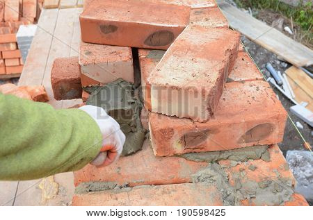 Bricklayer Worker Installing Red Blocks and Caulking Brick Masonry Joints Exterior Wall with Trowel putty Knife. Bricklaying Masonry. Brick masonry.