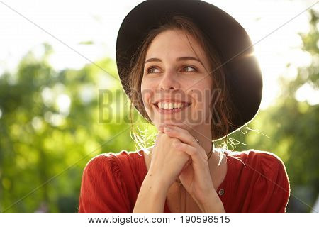 Close-up Portrait Of Pleased Woman With Pure Skin, Dark Eyes And Sincere Smile Wearing Summer Hat An