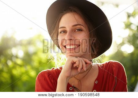 Happy Woman With Keen Eyes And Gentle Smile Wearing Summer Hat Holding Sunglasses In Hand Resting Ou