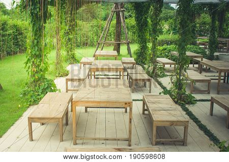 Wooden chair and table in beautiful garden at outdoor. (Autumn filter effect)
