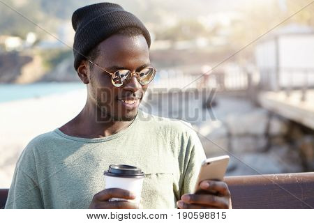 Smiling Black African Male In Glasses And Trendy Cap Tasting Delicious Coffee And Texting Friends Us