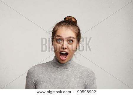 Headshot Of Bug-eyed Astonished Young Caucasian Pretty Woman Wiht Hair Bun Screaming In Shock And Ex