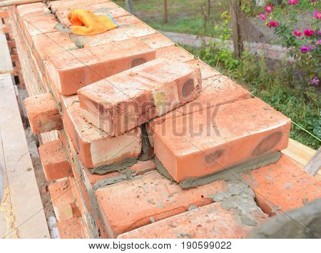 Bricklaying Brickwork. Bricklaying on House Construction Site. Building Home wall from Bricks. Bricklayer Worker Installing Red Blocks and Caulking Brick Masonry Joints Exterior Wall.