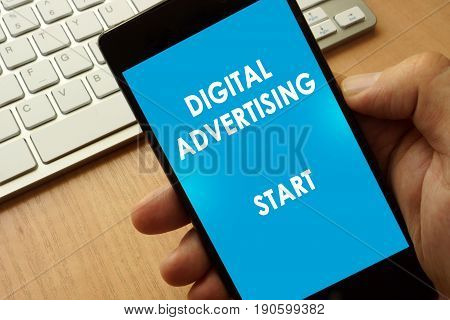 Hands holding phone with page Digital advertising.