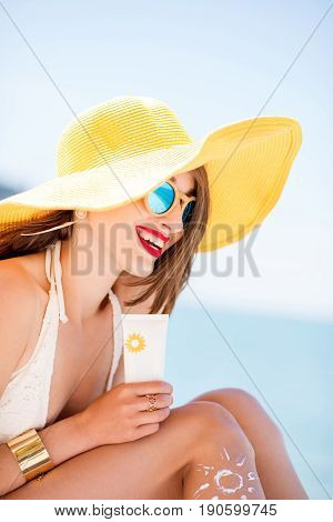 Beautiful smiling woman in yellow hat sunbathing holding a bottle with sunscreen UV protective lotion on the beach