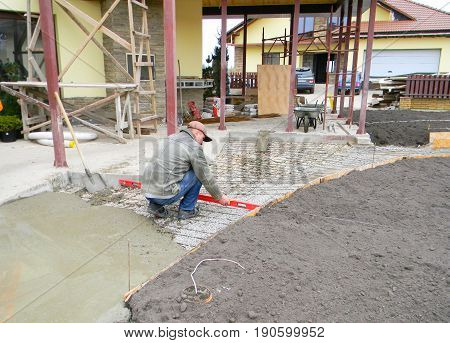 KYIV UKRAINE - JUNE 12 2017: Contractor builder building new concrete pavement and measure path foundation with spirit level for garden pathway and house terrace.