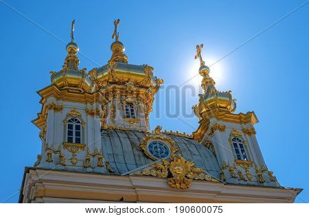 The domes of the church building. The domes are covered with gilding, they are crowned with crosses. The photo is made in the backlight. Petergof, Russia