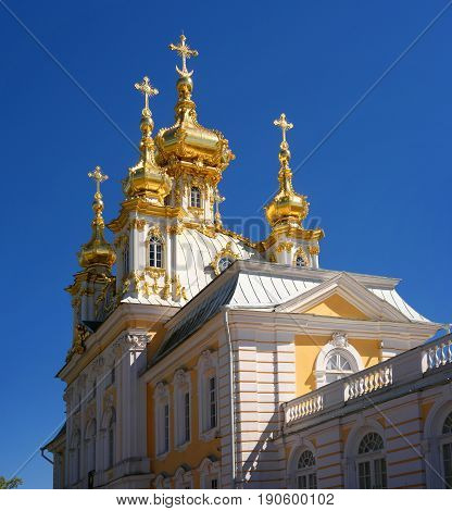 The domes of the church building. The domes are covered with gilding, they are crowned with crosses. Petergof, Russia