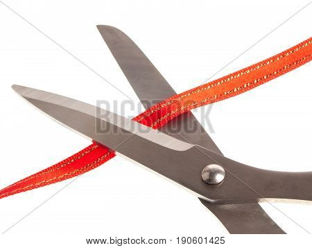 Open pair of scissors cutting red tape isolated on white background