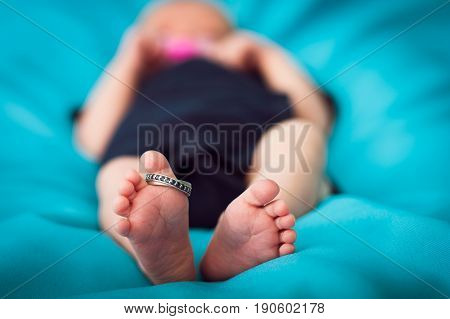 Closeup of newborn feet with a wedding ring. Family photography.