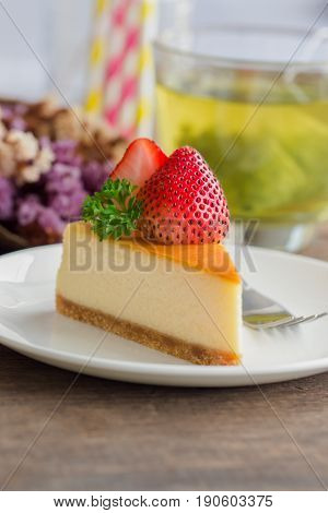 Homemade New York cheesecake on white plate decorated by fresh strawberry and parsley. Moist and smooth classic style baked cheesecake. Copy space background of delicious strawberry New York cheesecake. Piece of strawberry cheesecake.