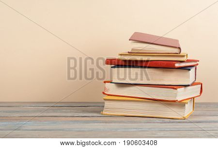 Book stacking. Open hardback books on wooden table and beige background. Back to school. Copy space for ad text.