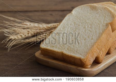 Sliced bread stack on wood plate. Homemade bread for breakfast put on rustic wood table. Soft and sticky homemade bread for delicious toast in breakfast. Homemade bakery background with copy space. Delicious and soft homemade bread.