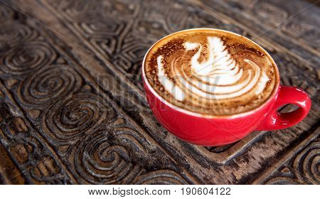 Cup of tasty cappuccino is standing on the wooden textured table. There is nice swan is painted on the top of the latte. Cappuccino is in the red cup its isolated.