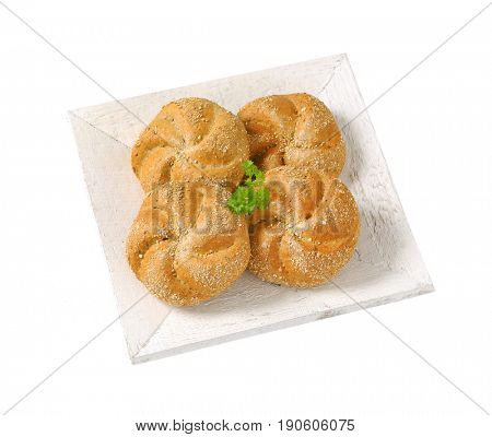 four whole wheat buns  on white wooden plate