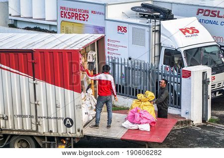 Kota Kinabalu,Sabah-May 27,2017:Pos laju Express deliverer loading boxes into the truck in Kota Kinabalu,Sabah,Malaysia.It is the leading courier company & has the widest network coverage in Malaysia.