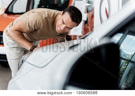 Smiling man watching at headlamps in automobile. He choosing it for purchase in salon