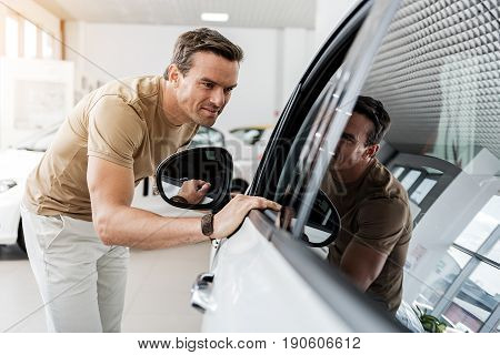 Smiling man expressing concernment while looking at passenger compartment through window of automobile