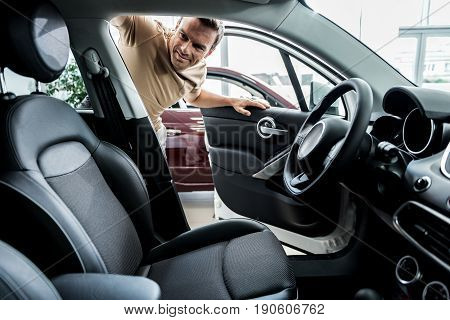 Male expressing happiness while watching at passenger compartment of new automobile