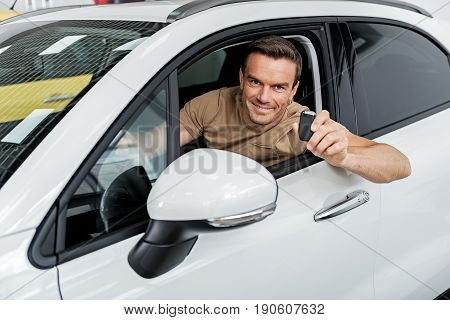 Portrait of man demonstrating gladness while holding technical tool. He sitting in automobile