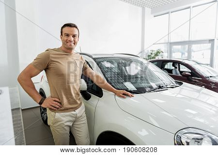Portrait of male expressing gladness while standing near modern vehicle in automobile showroom. Purchase concept