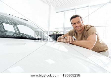 Portrait of man demonstrating happiness while leaning on white bonnet in car dealership
