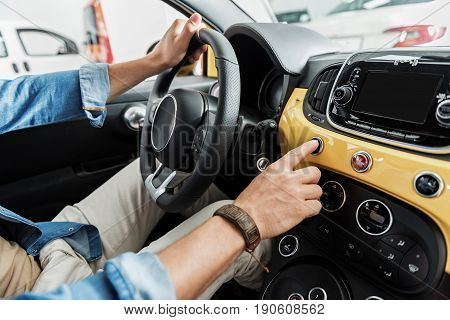 Close up man arm pressing on panel of modern car while holding rudder