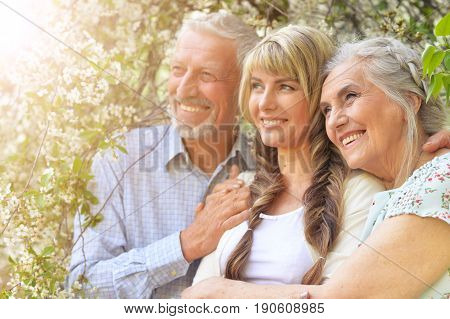 Family portrait of parents with adult daughter in spring trees