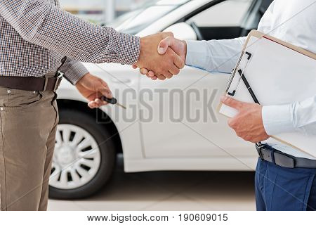 Close up hands of men shaking hands. They standing near new vehicle in car dealership