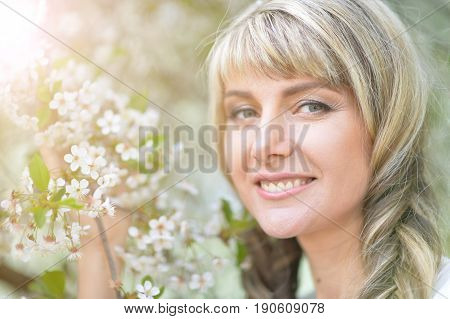 Portrait of beautiful young woman holding blooming tree brunch