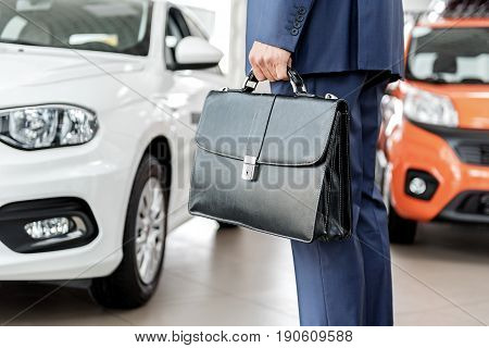 Close up leathern suitcase which holding male in hand. He situating in car dealership
