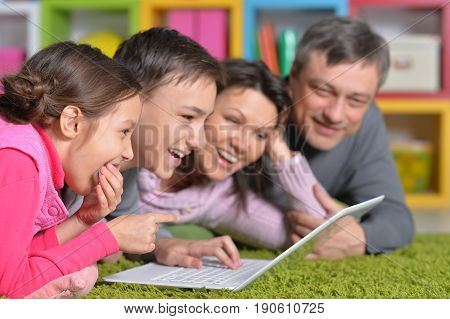 Big happy family lying on floor in front of laptop