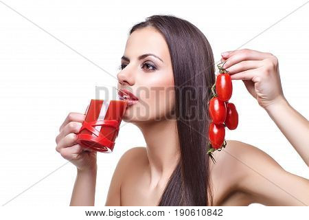 beautiful brunette young woman holding glass with tomato juice and bunch of cherry tomatoes. isolated on white background. copy space.