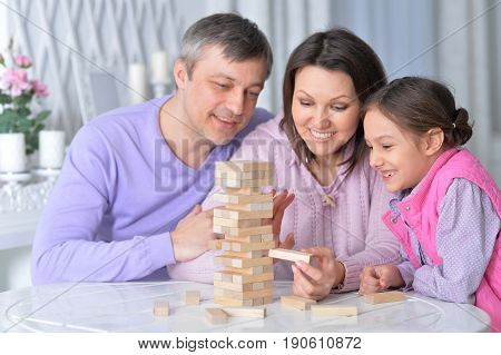 Happy family sitting at table and playing with wooden blocks