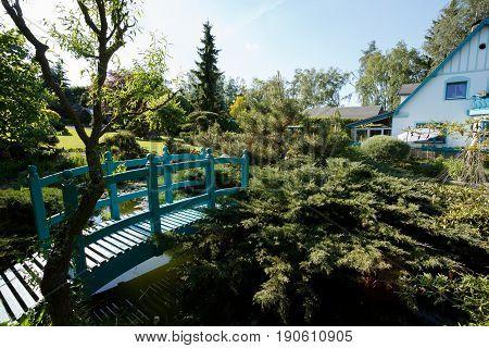 Small Green Footbridge Over A Spring Garden Pond