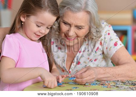 Portrait of a grandmother collecting puzzle with her granddaughter