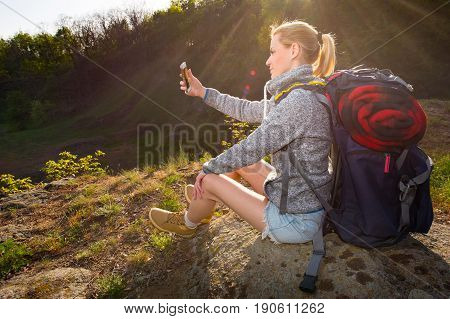 Woman with backpack resting and taking photo of beautiful landscape in a hike in the mountains. Travel vacation holidays and adventure concept. Forest landscape background