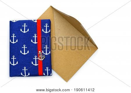 Beautiful small notebook in ship anchor design cover with red ribbon closure lying on vintage paper envelope. Copy space. Isolated on white background.