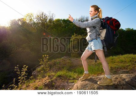 A Girl with backpack taking photo of beautiful landscape with mobile phone in a hike in the forest. Travel vacation holidays and adventure concept. Forest landscape background