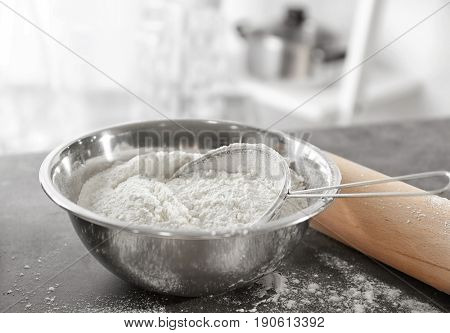 Sieve and bowl with flour on blurred background, close up