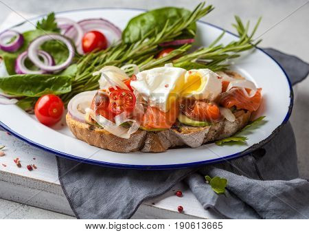 Egg poached and salmon on toast with vegetables. Egg benedict in rustic style.