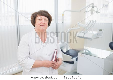 Portrait of midle aged female dentist , standing in her dentist office and holding a book or diary