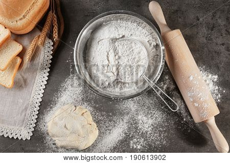 Sieve and bowl of flour on dark table, top view