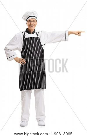 Full length portrait of a chef pointing right isolated on white background