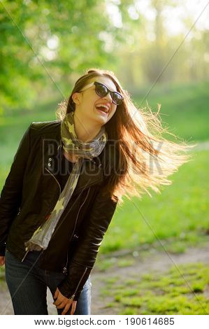 Portrait of the young cheerful woman in beams of the sun. Wind has disheveled a long dark hair. Against the background of the greenery of the spring park.